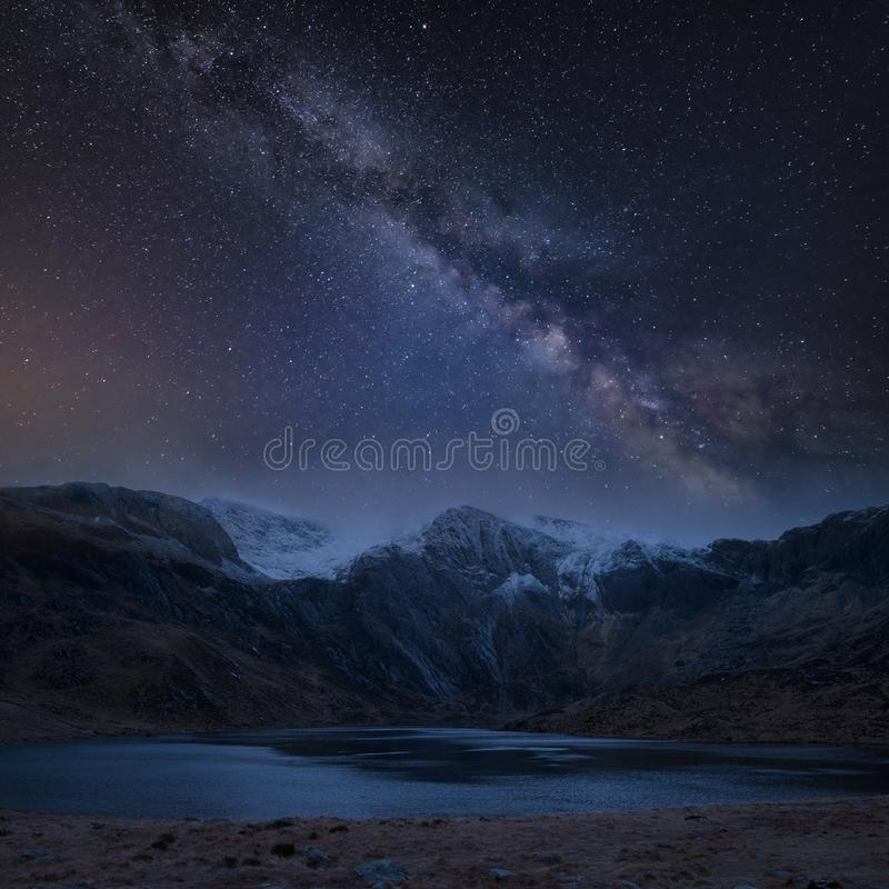 Composite image of Winter landscape of snowcapped Mountain Range at night with Milky Way above. Digtial composite image of Winter landscape of snowcapped stock photos