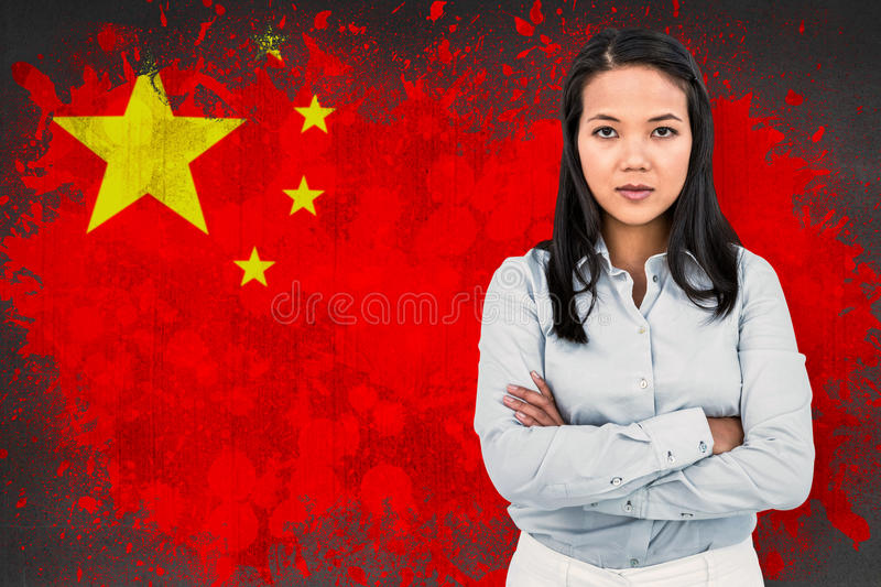 Composite image of woman with arms crossed looking at camera. Woman with arms crossed looking at camera against china royalty free stock photography