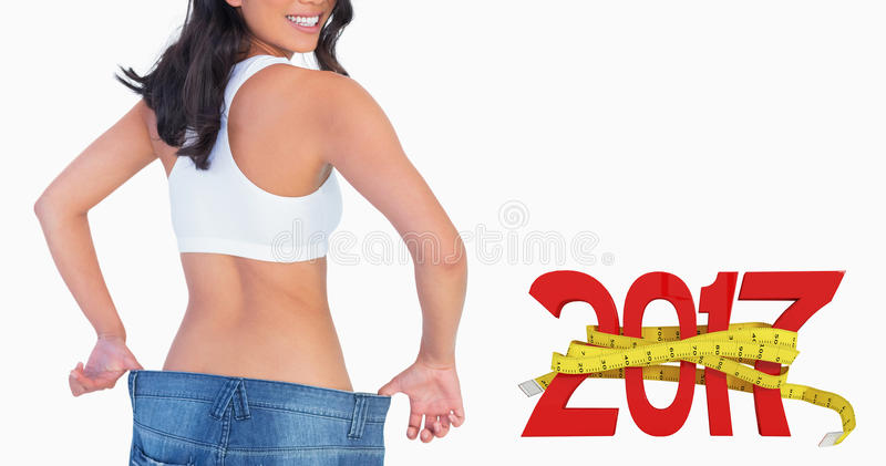Composite image of woman holding her too big jeans smiling stock photo