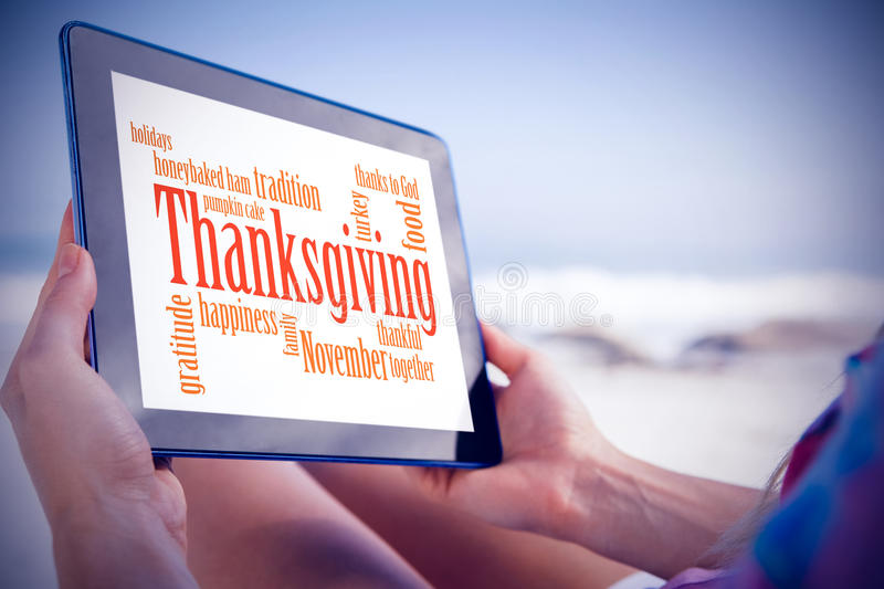 Composite image of woman sitting on beach in deck chair using tablet pc. Woman sitting on beach in deck chair using tablet pc against thanksgiving words stock photography