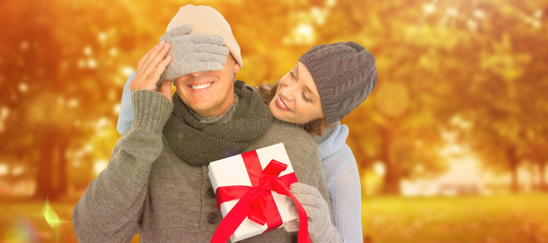 Composite image of woman surprising husband with gift. Woman surprising husband with gift against autumn scene stock photo