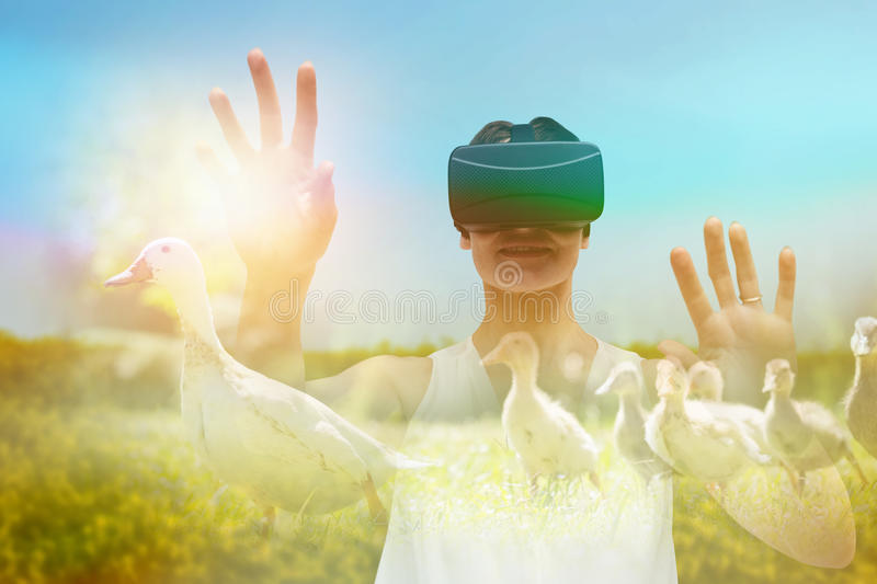 Composite image of woman using virtual reality simulator glasses stock photography