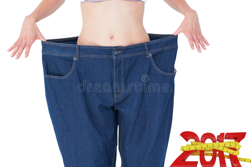 Composite image of woman wearing too large pants. Woman wearing too large pants against digitally generated image of new year with tape measure stock photos