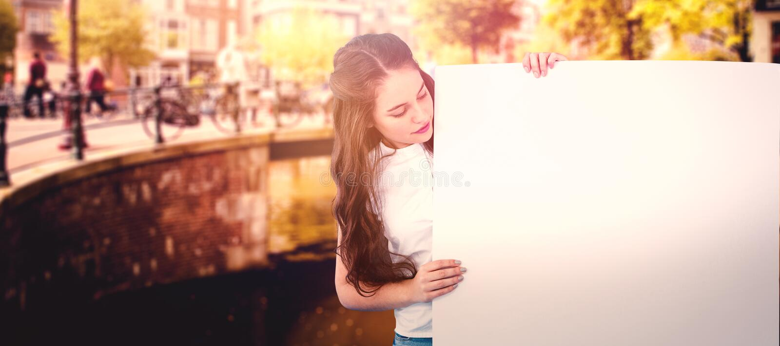 Composite image of women holding blank poster. Women holding blank poster against bridge in amsterdam stock images