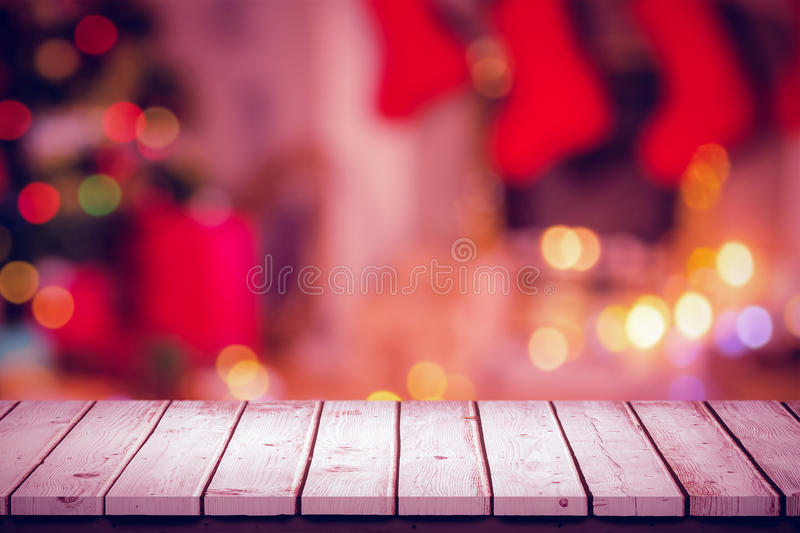 Composite image of wooden table. Wooden table against tealight candles burning stock image