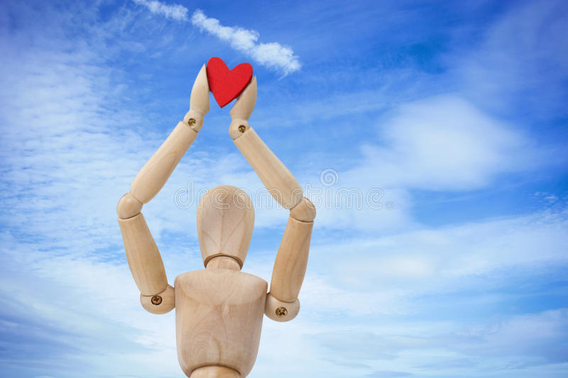 Composite image of wooden three dimensional figurine holdingred heart on top. Wooden three dimensional figurine holdingred heart on top against low angle view of stock images