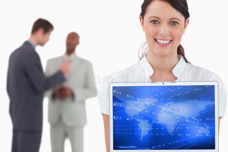Composite image of world map with shares on blue background. World map with shares on blue background against tradeswoman showing laptop with colleagues behind stock images