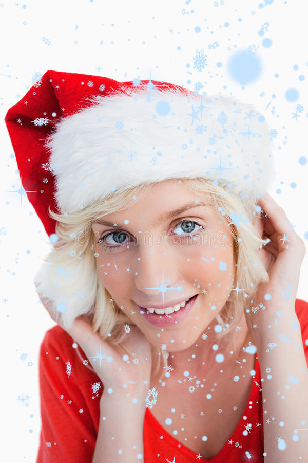 Composite image of young blonde woman putting on the santa claus hat royalty free stock photography