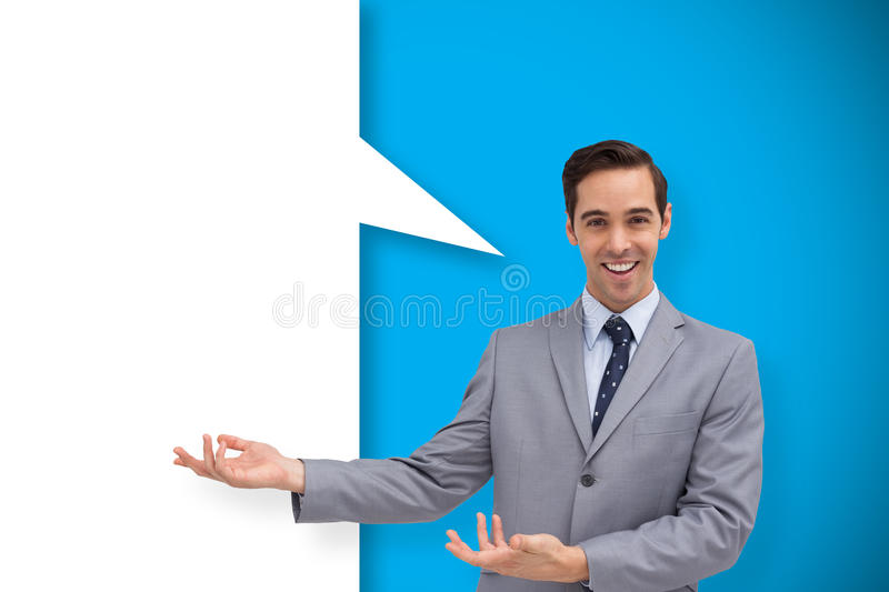 Composite image of young businessman presenting something with speech bubble stock image