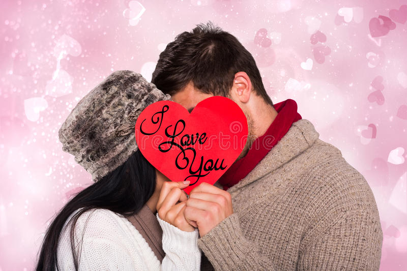 Composite image of young couple kissing behind red heart royalty free stock images