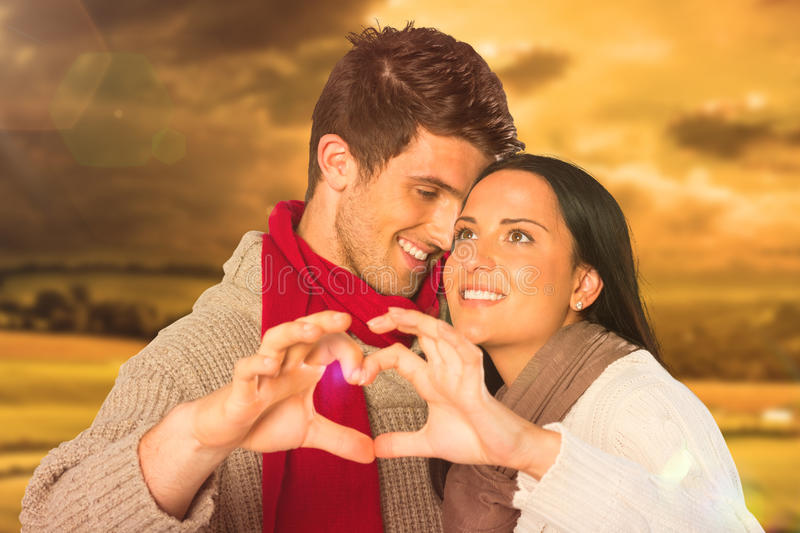 Composite image of young couple making heart with hands stock photo
