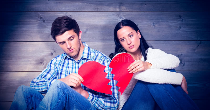 Composite image of young couple sitting on floor with broken heart stock photography