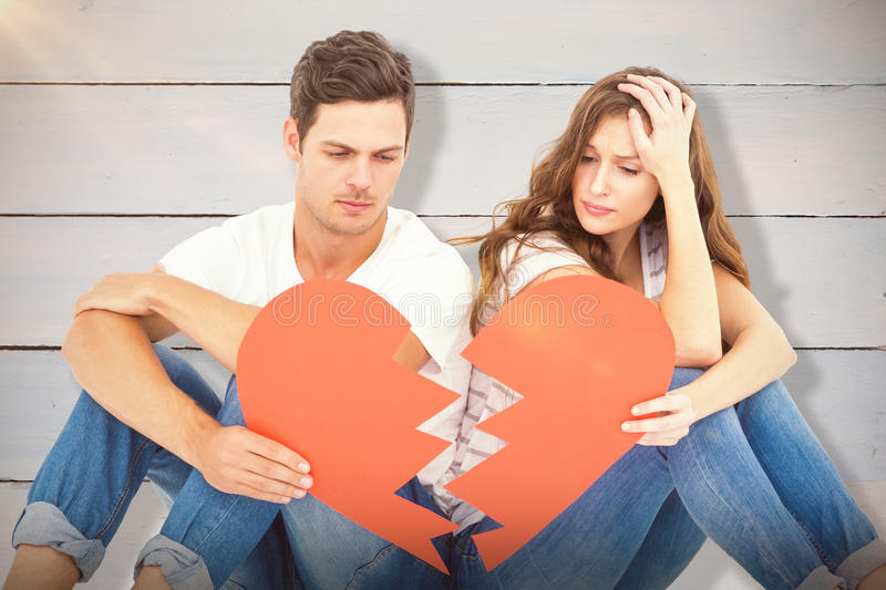 Composite image of young couple sitting on floor with broken heart shape paper. Young couple sitting on floor with broken heart shape paper against painted blue stock photos