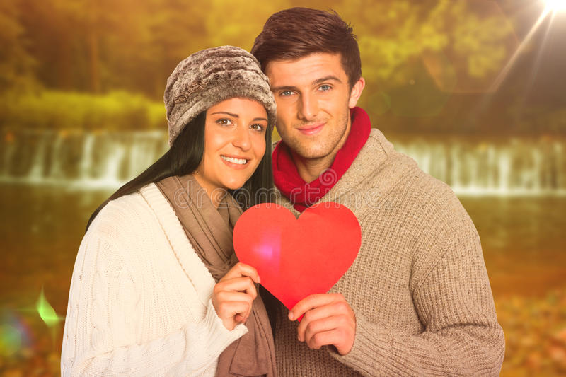 Composite image of young couple smiling holding red heart stock photos
