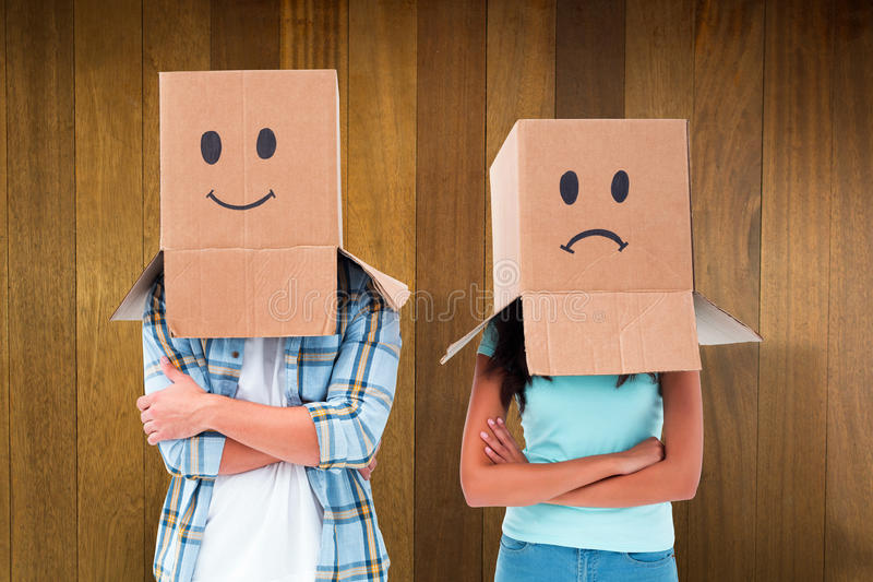 Composite image of young couple wearing sad face boxes over head stock image