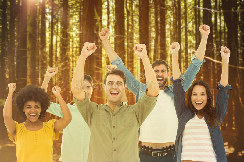 Composite image of young creative business people gesturing arm up. Young creative business people gesturing arm up against trees in a woods stock images