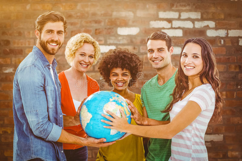 Composite image of young creative business people with a globe. Young creative business people with a globe against brick wall stock photo