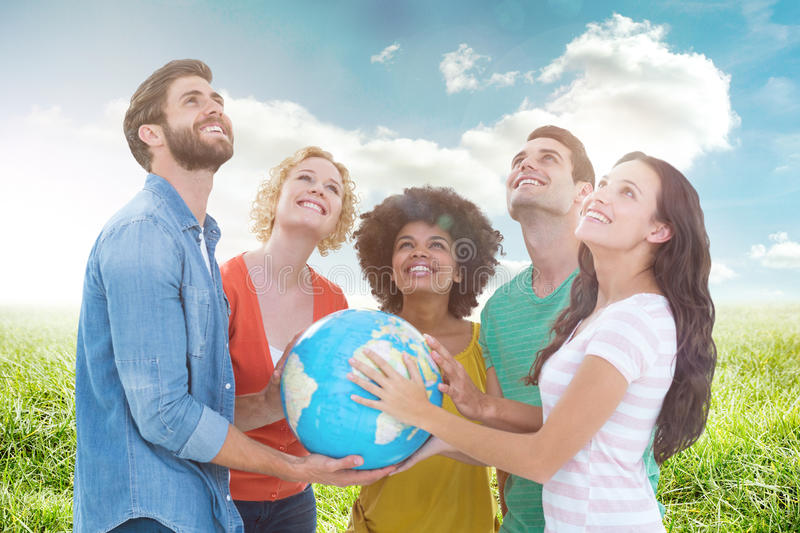 Composite image of young creative business people with a globe. Young creative business people with a globe against sunny landscape stock photo