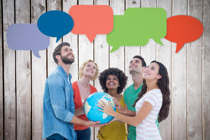 Composite image of young creative business people with a globe. Young creative business people with a globe against wooden planks stock image