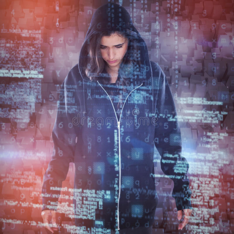 Composite image of young female hacker in black hoodie standing stock photography