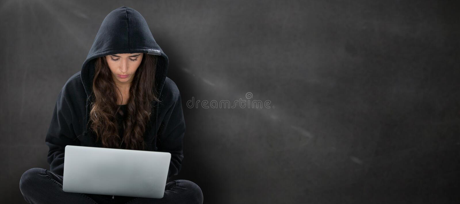 Composite image of young female hacker using laptop while sitting royalty free stock images