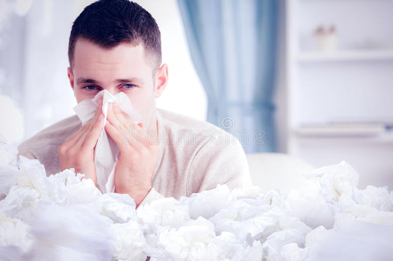Composite image of young man blowing his nose stock photos
