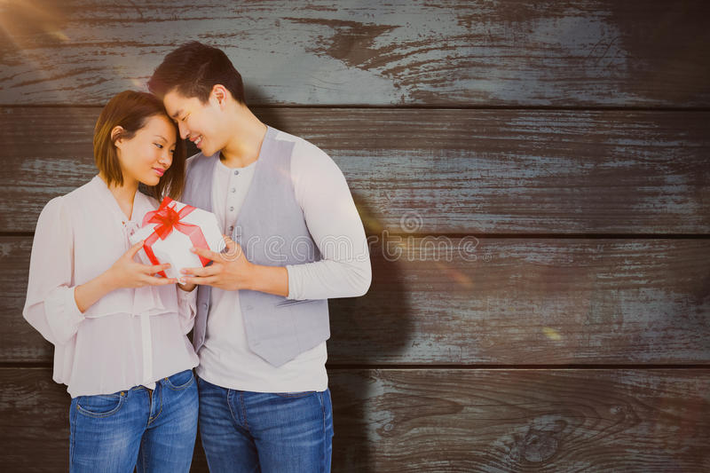Composite image of young man giving present to woman royalty free stock images