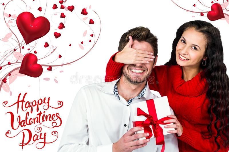 Composite image of young woman covering eyes of partner holding gift royalty free stock photo