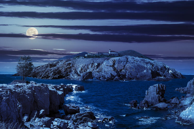 Composite island with hills and castle at night. Fairytale composite of rocky shore and island with hills and castle with red roofs at night in full moon light stock photos