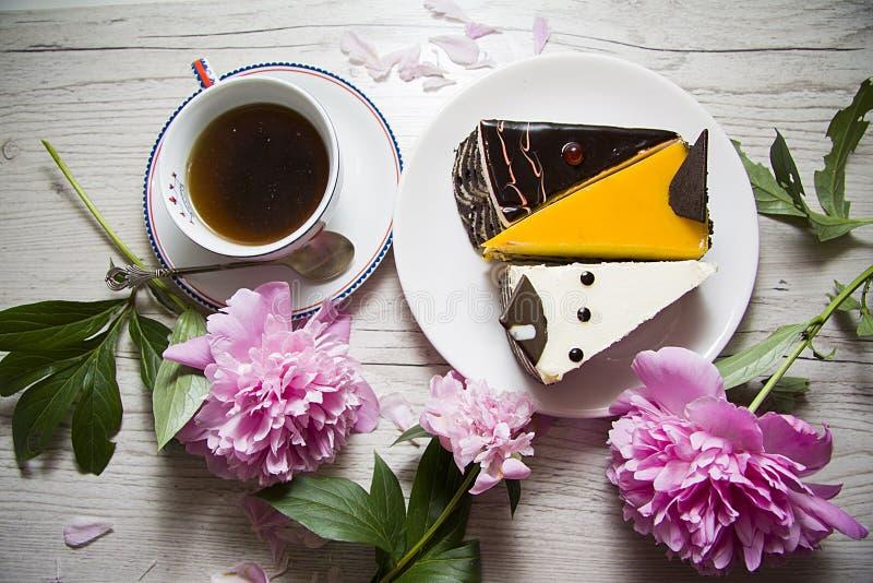 Compositiom romántico del postre con la peonía y los pasteles de queso fotografía de archivo libre de regalías