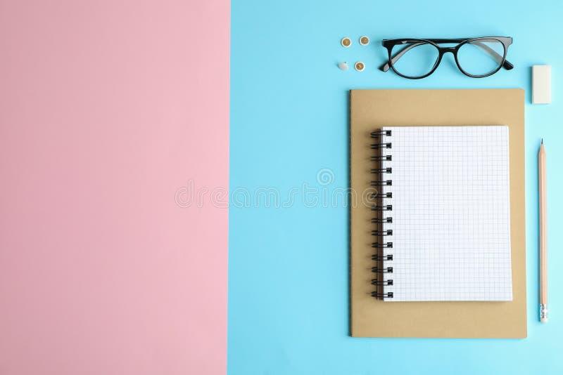 Composition étendue plate avec des accessoires de bureau sur le fond de deux tons photos stock