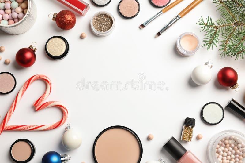 Composition étendue plate avec des produits de maquillage et décor de Noël sur le fond blanc images stock