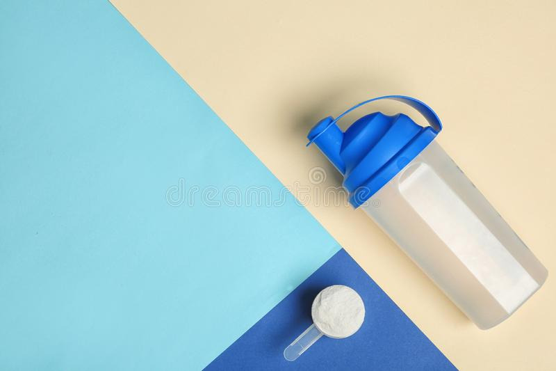 Composition étendue plate avec la poudre, la bouteille et l'espace de protéine pour le texte sur le fond de couleur photos stock