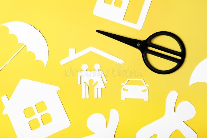 Composition étendue plate avec la silhouette de papier de la famille et des ciseaux sur le fond de couleur images stock