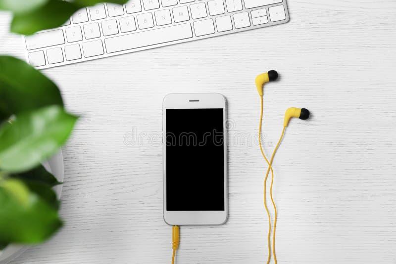 Composition étendue plate avec le clavier d'écouteurs, de smartphone et d'ordinateur sur le fond en bois blanc photos libres de droits