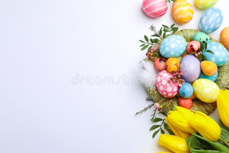 Composition étendue plate avec le nid, les oeufs de pâques, les plumes et les fleurs sur le fond de couleur photos stock