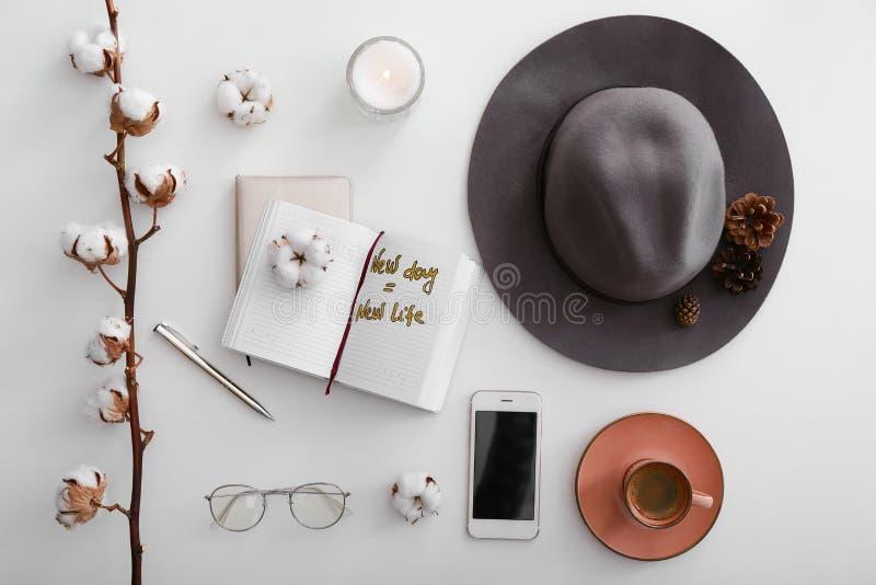 Composition étendue plate avec le téléphone portable, le chapeau, la bougie brûlante et le carnet ouvert sur le fond blanc photos libres de droits