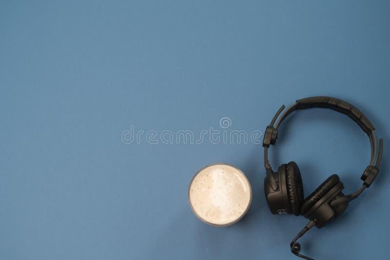Composition étendue plate avec les écouteurs, le microphone et le café sur un fond bleu Concept Podcast ou webinar photo stock