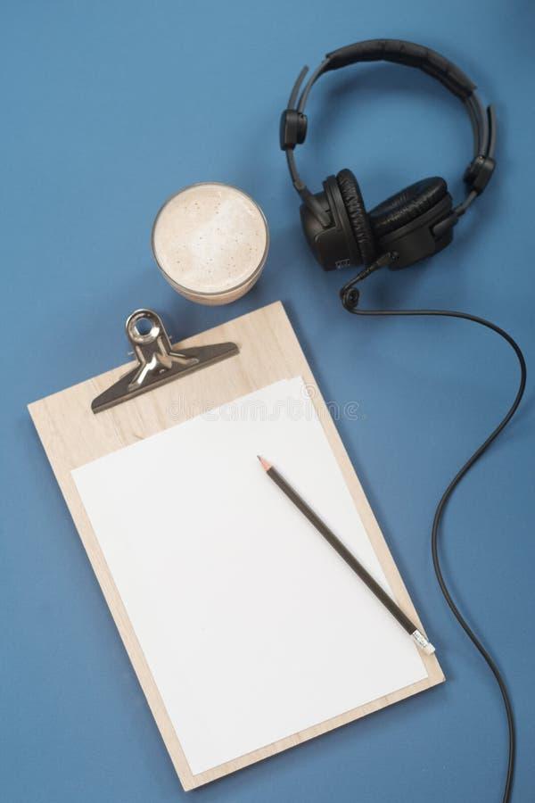 Composition étendue plate avec les écouteurs, le microphone et le café sur un fond bleu Concept Podcast ou webinar image libre de droits