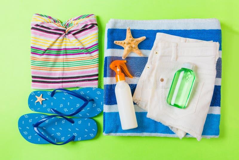 Composition étendue plate avec les accessoires bleus de plage sur le fond de couleur verte Fond de vacances d'?t? Articles de vac images stock