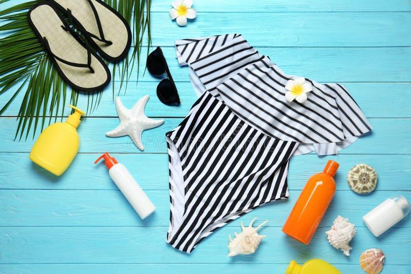 Composition étendue plate avec les accessoires rayés de maillot de bain et de plage sur en bois bleu image stock