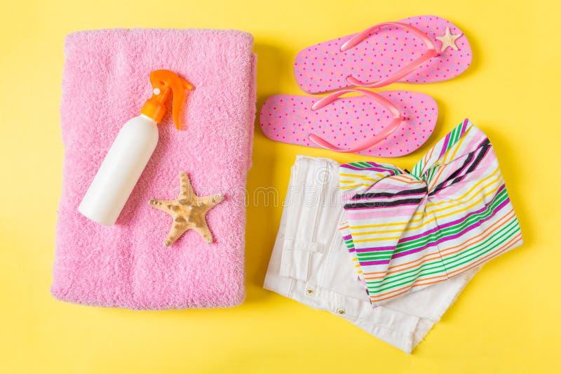 Composition étendue plate avec les accessoires roses de plage sur le fond jaune de couleur Fond de vacances d'?t? Articles de vac photo libre de droits