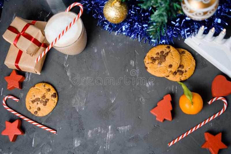 Composition étendue plate avec les biscuits, le décor et le cacao de Noël sur la table noire photographie stock libre de droits