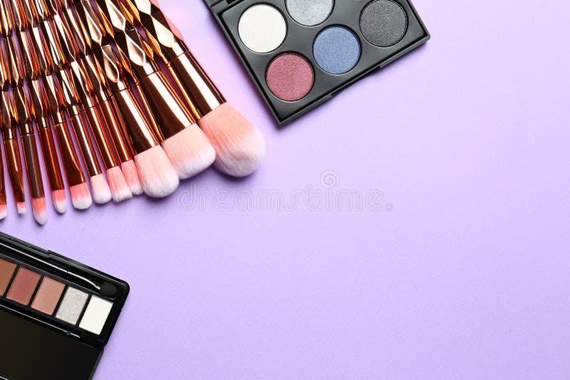 Composition étendue plate avec les brosses de maquillage et les palettes professionnelles de fard à paupières sur le fond lilas image stock