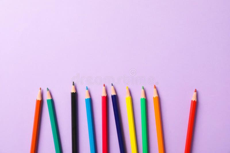 Composition étendue plate avec les crayons multicolores sur le fond violet photos stock