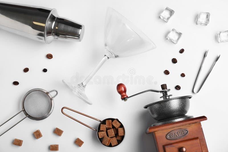 Composition étendue plate avec les ingrédients de Martini d'expresso et l'équipement de barre sur le fond blanc photographie stock