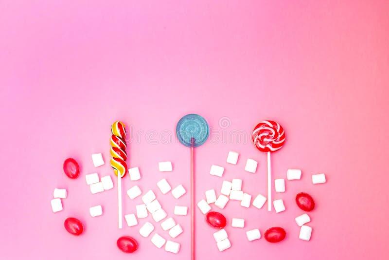 Composition étendue plate avec les lucettes et les guimauves délicieuses et espace pour le texte sur le fond rose photo libre de droits