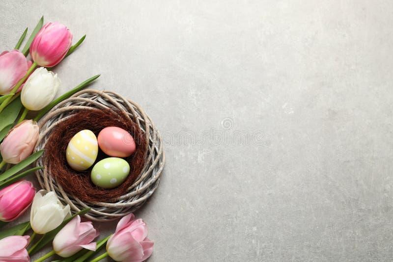 Composition étendue plate avec les oeufs de pâques peints dans le nid en osier et les tulipes sur le fond de couleur image stock