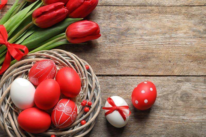 Composition étendue plate de nid avec les oeufs et les fleurs de pâques peints sur la table en bois images stock