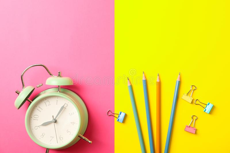 Composition with alarm clock, pencils and clips on two tone background. Space for text stock photo